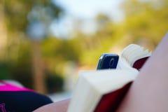 Mujer distraída con el teléfono móvil cuando libro y sol de lectura foto de archivo libre de regalías