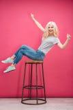 Mujer divertida alegre que se sienta en la silla Fotos de archivo libres de regalías