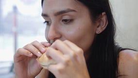 Mujer divertida bastante joven de Latina que come la hamburguesa interior Alimentos de preparación rápida almacen de metraje de vídeo
