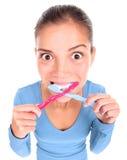 Mujer divertida con dos dientes que aplican con brocha del cepillo de dientes Imagenes de archivo