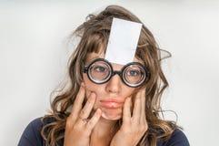 Mujer divertida con el papel pegajoso blanco en blanco sobre su frente fotos de archivo libres de regalías