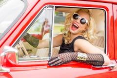 Mujer divertida con las gafas de sol elegantes que conducen un coche fotografía de archivo libre de regalías