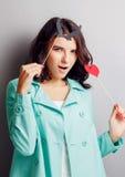 Mujer divertida con los cuernos que llevan a cabo un corazón Imágenes de archivo libres de regalías