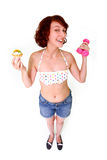 Mujer divertida con pesas de gimnasia y la torta Imagenes de archivo