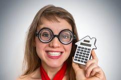 Mujer divertida de la escuela del friki o del empollón con la calculadora Fotografía de archivo libre de regalías