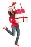 Mujer divertida de la Navidad en la prisa que se ejecuta con los regalos Fotografía de archivo