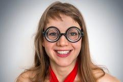 Mujer divertida del friki o del empollón aislada en fondo gris Foto de archivo