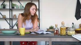 Mujer divertida del jengibre que lee el libro culinario y que baila en cocina moderna durante proceso de cocinar en la mañana almacen de video