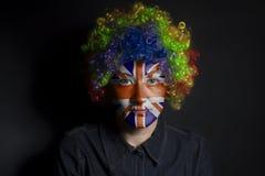 Mujer divertida del payaso con la bandera británica pintada fotos de archivo