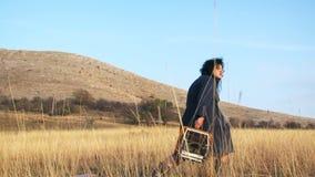 Mujer divertida en el arrastramiento negro con la máquina de escribir en metrajes