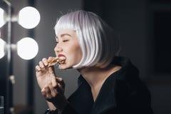 Mujer divertida en peluca rubia que come la pizza en vestuario Fotos de archivo libres de regalías