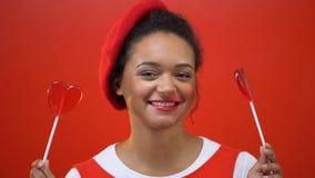 Mujer divertida en rojo que se jacta con dos caramelos en forma de corazón, símbolo de las tarjetas del día de San Valentín del s metrajes