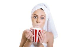Mujer divertida envuelta en una toalla que bebe té caliente Foto de archivo libre de regalías