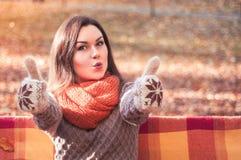 Mujer divertida joven con los pulgares para arriba en un banco en un parque del otoño imagen de archivo