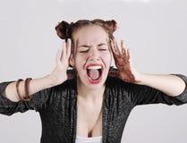 Mujer divertida joven del inconformista que muestra la lengua, el grito y la sorpresa con la cara divertida de la emoción Imagen de archivo