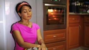 mujer divertida que cocina en la cocina, comiendo platos almacen de metraje de vídeo