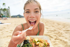 Mujer divertida que come la comida sana de la ensalada en la playa imagenes de archivo