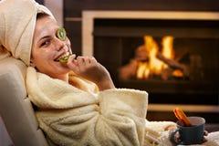 Mujer divertida que come la fruta de la máscara facial fotos de archivo