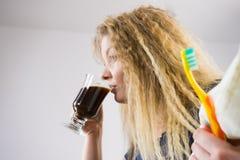 Mujer divertida que es último café de consumición Imagen de archivo