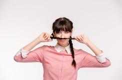 Mujer divertida que hace el bigote con la coleta Imagen de archivo