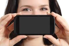 Mujer divertida que muestra una pantalla elegante en blanco del teléfono Fotografía de archivo libre de regalías