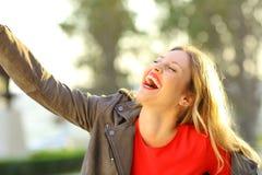 Mujer divertida que ríe y que bromea en un parque Imagenes de archivo