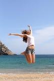 Mujer divertida que salta en una playa del paraíso Fotos de archivo