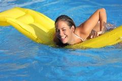Mujer divertida que se baña en una piscina que juega con un colchón Fotografía de archivo