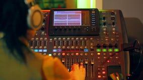 Mujer DJ en auriculares detrás de una consola de mezcla que trabaja en la iluminación del color almacen de metraje de vídeo