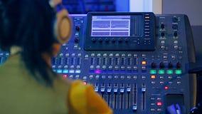 Mujer DJ en auriculares detrás de una consola de mezcla que trabaja en la iluminación del color almacen de video