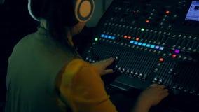 Mujer DJ en auriculares detrás de una consola de mezcla que trabaja en la iluminación del color Filmación de la parte posterior almacen de video