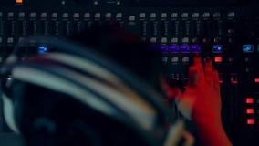 Mujer DJ en auriculares detrás de una consola de mezcla que trabaja en la iluminación del color metrajes