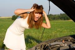 Mujer doblada sobre el motor de coche fotos de archivo