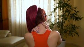 Mujer dolida que le da masajes detrás del cuello para curar el dolor en casa almacen de metraje de vídeo