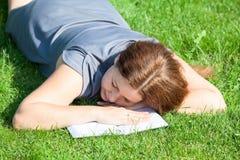 Mujer dormida mientras que libro de lectura Imagen de archivo