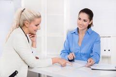 Mujer dos en el escritorio - reunión de negocios financiera. imagenes de archivo