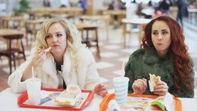 Mujer dos que come la comida basura en restaurante de los alimentos de preparación rápida almacen de video