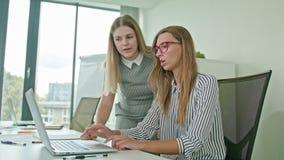 Mujer dos que discute ideas usando el ordenador portátil metrajes