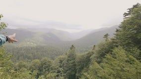 Mujer dos que se coloca en pico de montaña y que mira en las colinas verdes y bosque almacen de video