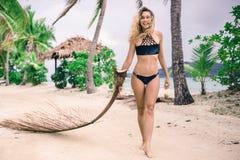 Mujer draging la rama secada de la palma en la playa arenosa de la pequeña isla Imagen de archivo