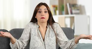 Mujer dudosa que encoge hombros a la cámara almacen de video