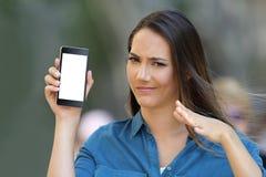 Mujer dudosa que muestra una pantalla en blanco del teléfono Imagenes de archivo