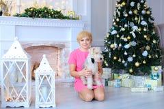 Mujer dulce hermosa que se sienta en el piso, sosteniendo el perro en backgroun Fotografía de archivo libre de regalías