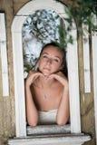 Mujer dulce que se inclina en una construcción de la ventana de la decoración fotografía de archivo