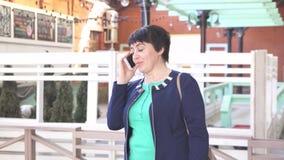 Mujer durante 40 años que habla en el paisaje urbano del teléfono metrajes