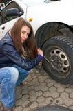 Mujer durante el cambio de la rueda Imagen de archivo libre de regalías