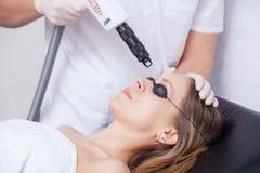 Mujer durante terapia del laser de la cara en cosméticos Imágenes de archivo libres de regalías