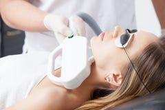 Mujer durante terapia del laser de la cara en cosméticos Fotos de archivo libres de regalías