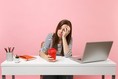 Mujer durmiente cansada de los jóvenes que se inclina a mano sosteniendo la taza de café o de té mientras que trabajo y sentarse  imagen de archivo