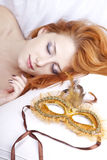 Mujer durmiente cerca de la máscara del carnaval. Foto de archivo